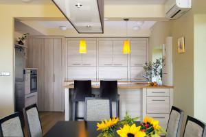 Barevné akcenty vjinak střídmě pojatém interiéru představují žlutá svítidla nad kuchyňským pultem. Majitelé je stylově podpořili výběrem květin na jídelní stůl. FOTO ROBERT ŽÁKOVIČ