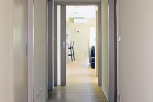 Úzká dlouhá chodba je spojnicí všech místností vdomě. Když do ní vstoupíte od hlavního vchodu, vpravo se nám otevře pohled na společný obytný prostor. FOTO ROBERT ŽÁKOVIČ