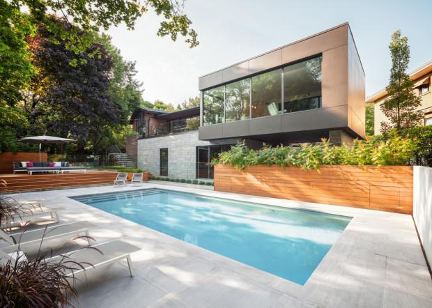 V exteriéru si architekti Louis Thellend a Lisa-Marie Fortin pohráli s kontrastními barvami. Přístavba, obložená antracitově černými betonovými panely se nádherně odráží v bazénu, lemovaném dlažbou z bílého vápence. Opalovací terasu pak tvoří prkna z cedrového dřeva.