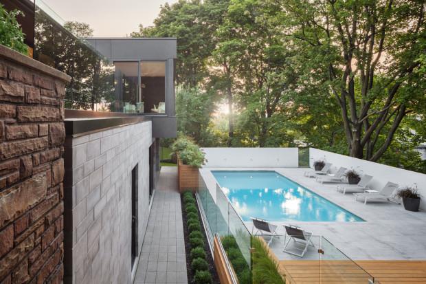 Přiléhající plochu pak tvoří na bílo obarvené betonové dlaždice. Textura a odstín použitých materiálů se nádherně doplňují s působivou zelenou klenbou vzrostlých javorů. Díky nim si mohou majitelé vychutnávat tuto oázu navzdory faktu, že se nacházejí uprostřed města.