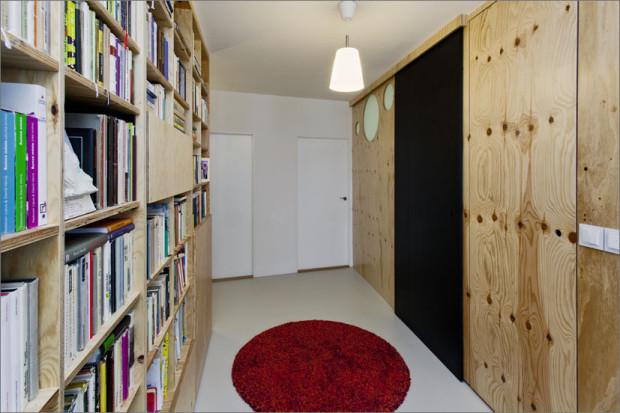 Prostorná chodba s vestavěnou knihovnou přes celou stěnu.