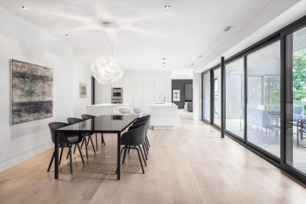 """Stejně jako v exteriéru, i v interiéru najdeme kontrast barev. Velkorysé bílé kuchyňské lince a podlaze ze světlého dřeva """"oponuje"""" tmavá sestava jídelního stolu a židlí, podpořená antracitovým hliníkovým rámem velkoformátových oken."""