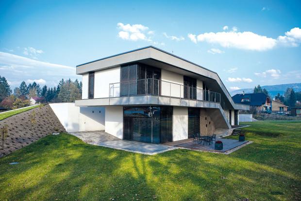 Praktický svah. Kzadní stěně garáže navezli zeminu získanou při terénních úpravách azakládání domu. Vznikl tak svah, který přirozeně chrání soukromí zahrady, azároveň ušetřili za odvoz zeminy. Na povrch teras zvolili odolné exotické dřevo. Foto Projektstudio