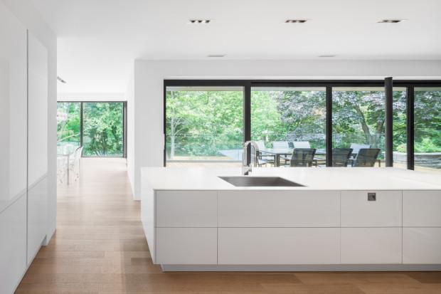 Černě orámovaný výhled do zeleně vytváří příjemný protiklad ke světlému, andělsky bělostnému interiéru kuchyně.