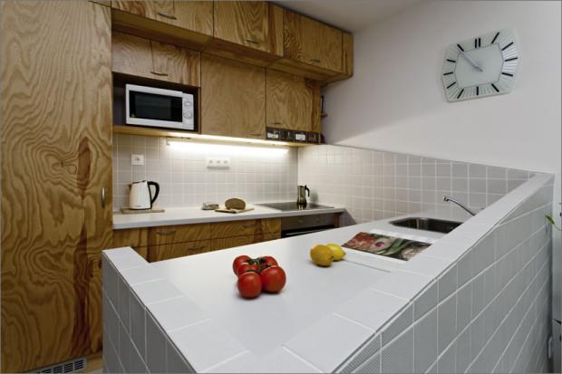 Výrazným prvkem je sešikmení, které řeší obložení stěn i ohraničení celé kuchyňské desky.