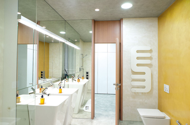 """Beze spár. Koupelnu uložnice rodičů barevně oživuje voděodolná stěrka vteplém odstínu žluté. Také zde zůstal architekt Kotek věrný prostorotvorné hře velkých hladkých ploch, při všech povrchových úpravách dodržel též praktickou zásadu """"beze spár"""". Foto Projektstudio"""