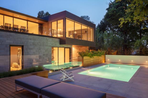 Osvětlený bazén se efektně odráží ve skleněné ploše zábradlí. Hra světel a tvarů se naplno rozehrává s pokračující nocí.