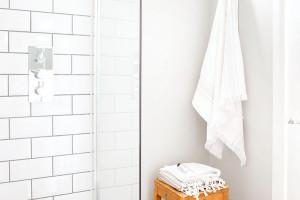 Magická kombinace šedé, bíléadřeva působí čistě, svěže azároveň útulně. Ani koupelna přitom není výjimkou vbarevném schématu bytu.