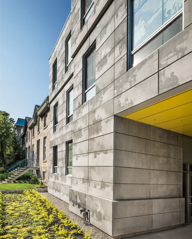 """Vstup do budovy je odkazem na typický prvek montrealské architektury, """"porte-cochère"""", chráněný průjezd určený koňským povozům, a poskytuje tak intimní přístup do budovy."""