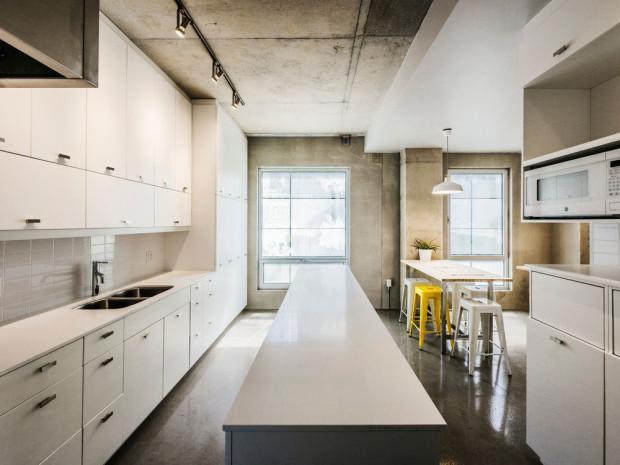 Kuchyně je vybavena jednoduše v minimalistickém duchu, bílé provedení dává vyniknout syrové kráse betonových ploch. I zde najdeme nenápadně zakomponovaný žlutý akcent v podobě barových stoliček.