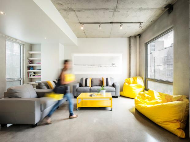 Ve společném obýváku (klubovně) mohou studenti využít pohodlné sezení s knihou. Vybrat si mohou mezi konzervativně šedými pohovkami, rozveselenými pruhovanými polštáři, a sytě žlutými sedacími vaky. Foto: Marc Cramer