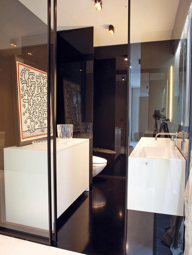 Koupelna pro hosty pro změnu včernobílé kombinaci a– za prosklenými dveřmi.