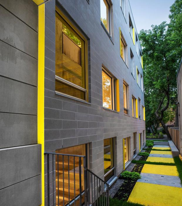Žlutý akcent na šedém pozadí se objevuje i v zadní části exteriéru: na fasádě a dvorku. Strohému vzhledu zděné budovy tak dodává svěží, mladistvý vzhled, což i odpovídá jejímu účelu. Foto: Marc Cramer