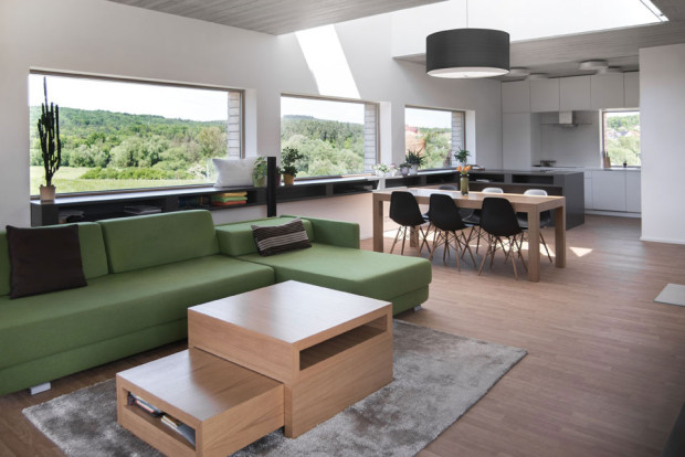 Velká místnost v sobě propojuje kuchyni, jídelnu a obývací prostor. Místo obrazu zde fungují okna s výhledem do krajiny a na okolní lesy. Tlumená barevnost vybavení koresponduje s okolní přírodou. Foto: Vojtěch Veškrna