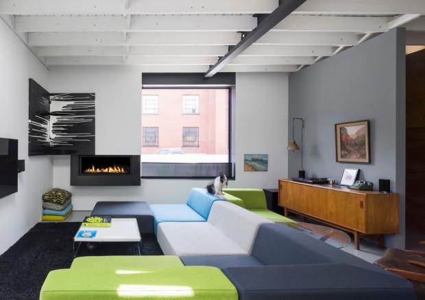 Obývák na rozdíl od zbytku interiéru hraje barvami díky velkorysé pohovce v pestrobarevném provedení. Foto: Stéphane Groleau