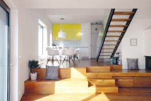 Dvě výškové úrovně denního prostoru oddělují multifunkční schody, které slouží ijako svébytné sezení ašikovné místo na odkládání. Otevřený denní prostor skuchyní ajídelnou se nachází na vstupní úrovni, opár schodů níž je položen obývák. FOTO Robert Žákovič