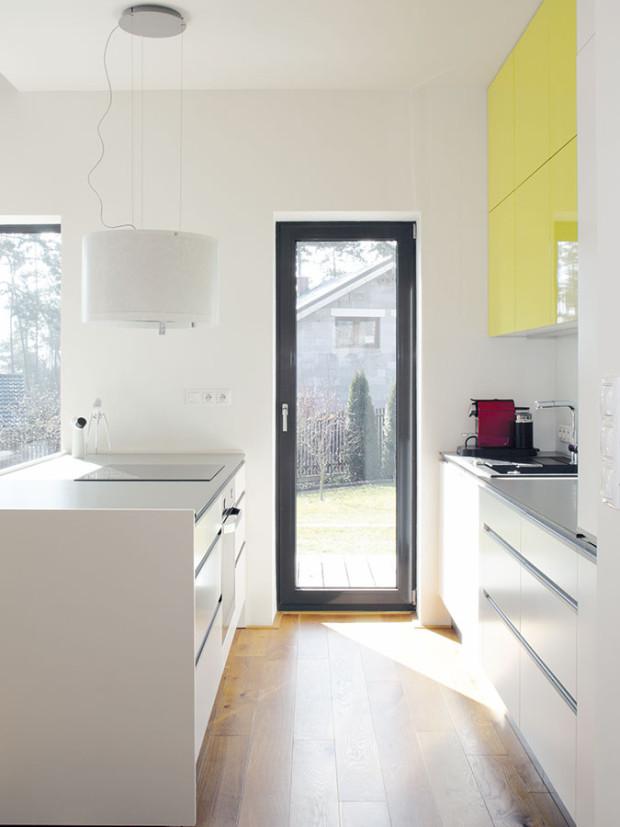 Kuchyňská linka svarným centrem na ostrově se nese vestejném duchu jako zbývající denní prostor – jednoduché, praktické zařízení, střídmé tvary ibarevnost aněkolik nápaditých detailů na oživení: žluté skříňky aoriginálně tvarovaná závěsná digestoř. FOTO Robert Žákovič