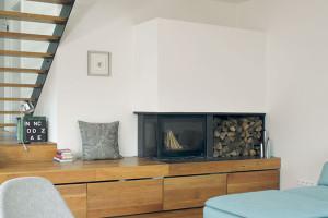 Víc by bylo zbytečné. Vinteriéru si architekt vystačil jen sněkolika barvami amateriály. Bílé stěny kontrastují solejovanou dubovou podlahou akovovými prvky sjednocenými antracitovou barvou – hliníkovými okenními rámy, ocelovými schodnicemi akonstrukcí krbu. Celek zjemňuje nábytek převážně vodstínech bílé, šedé abělavé. FOTO Robert Žákovič
