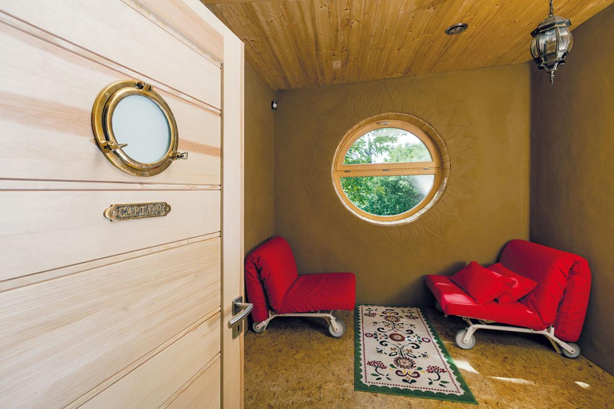 Pokoji pro hosty dominuje kulaté okno podobné těm na lodích, které si prosadila majitelka apro které tuto místnost nazývají kajuta. Iproto se rozhodli ladit ji vmírně námořnickém duchu. FOTO DANO VESELSKÝ