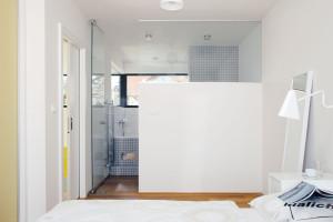 Ložnici rodičů vposchodí odděluje od koupelny en suite částečně skleněná příčka. Jeden vtipný nápad osvěžil oba prostory. FOTO Robert Žákovič