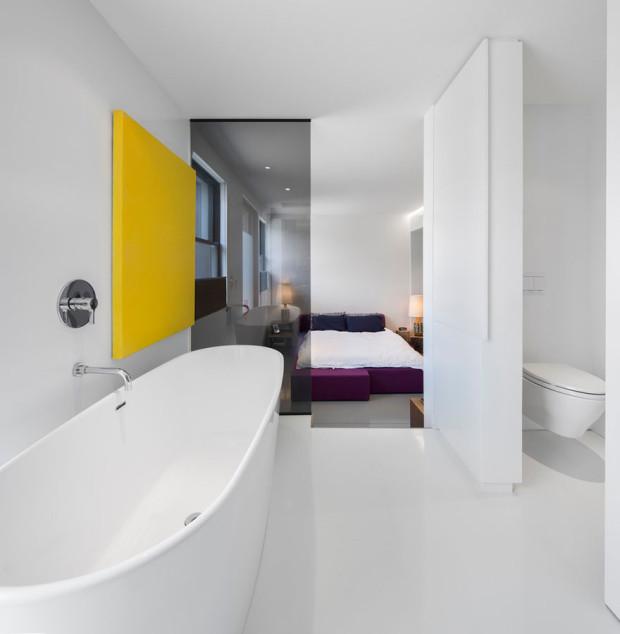 Soukromá koupelna pána domu je královstvím sama o sobě. Charakterizuje ji bohatá škála materiálů (barvený beton, exotické dřevo ipe, keramika, nerezový povrch a sklo) a barevný kontrast. Foto: Stéphane Groleau