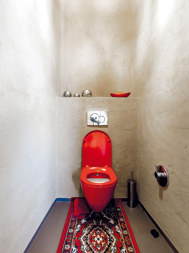 Kombinace hliněné omítky, červených astříbrných doplňků dodává toaletě specifický, příjemně působící charakter. FOTO DANO VESELSKÝ