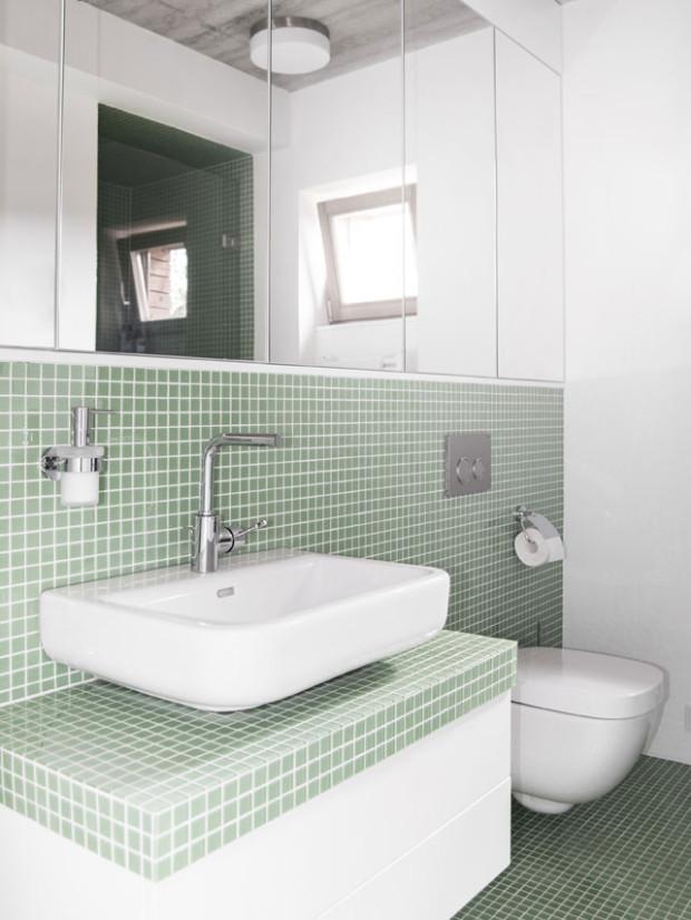 Světlá a střídmá koupelna zaujme kombinací velkých zrcadel a malého formátu mozaiky. Oblíbenost koupelnových mozaik stále roste, zde je aplikována jednoduše a funkčně v odstínu máty. Foto: Vojtěch Veškrna