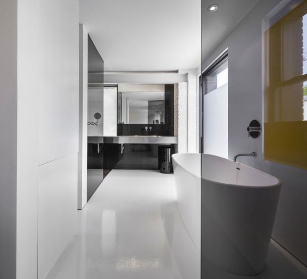 """Koupelna je dle moderních trendů pojata jako součást ložnice, tedy řešení en-suite. Cihlový obklad natřený na bílo svou """"hrubou strukturou"""" narušuje jednolitost hladkých materiálů. Foto: Stéphane Groleau"""