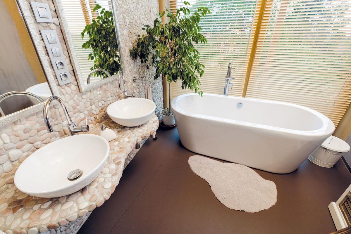 Hlavní koupelně vyčlenili poměrně velkorysý prostor. Upoutá hlavně netradiční stěnou apultem, které tvoří větší oblázky. FOTO DANO VESELSKÝ