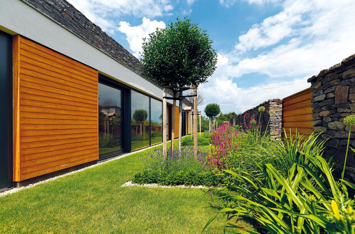 Plot tu není jen odškrtnutou povinnou výbavou, je promyšlenou kombinací kamene, dřeva avýsadby. Odděluje od ulice, chrání soukromí asceluje dům se zahradou do jednoho integrálního prostoru. FOTO DANO VESELSKÝ