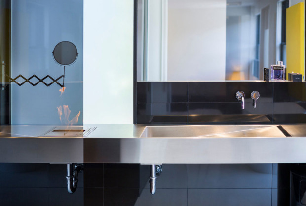 Oheň versus voda. Zajímavým prvkem, pro koupelnu ne úplně tradičním je biokrb zabudovaný v nerezové desce umyvadlového pultu. Foto: Stéphane Groleau