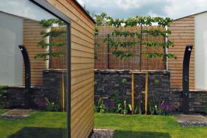 Zahradní domek (vlevo) ještě není dokončený. Jedna část je vyhrazena na zahradní nářadí, druhá se bude vlétě využívat jako venkovní kuchyňka, vsousedství má přibýt gril. Vzimě tu zase bude místo na zahradní nábytek zterasy. FOTO DANO VESELSKÝ