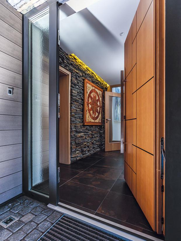 """Vdomě nenajdete typizované prvky – ivstupní dveře jsou vyrobeny na míru. Některé zvnitřních obkladů korespondují svenkovními – vtomto případě se do interiéru """"přepsal"""" kámen zfasády spodního podlaží. FOTO JIŘÍ ZERZOŇ"""
