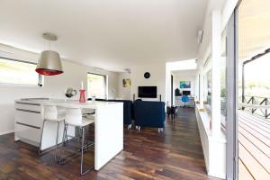Interiér si majitelé zařizovali sami. Je vněm cítit smysl pro jednoduchý, ale nápaditý design. Šetřilo se kusy ibarvami. Základní bílou doplňuje jen tmavě hnědá podlaha sdřevěným dekorem, modrý sedací nábytek ačerveno-žluté detaily. FOTO Dano Veselský