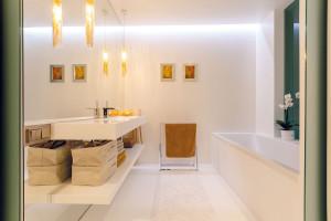 Bílo-zlatá koupelna je součástí ložnice ibudoáru (vanu od něj dělí pouze matné sklo). Svým pojetím se blíží zařízení obou místností, nejčastějí se využívá pro dlouhé uvolňující koupele, které smyjí stres z dlouhého pracovního dne. FOTO DANO VESELSKÝ