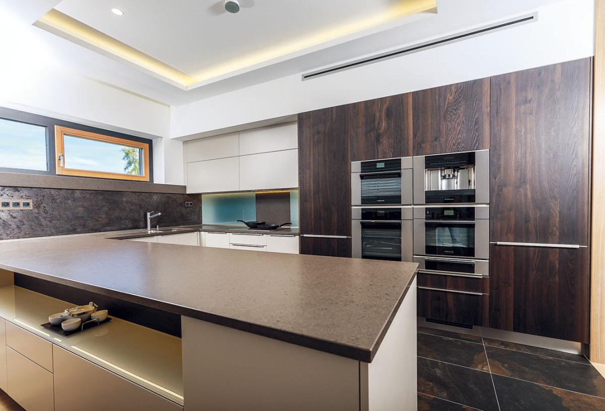 Kuchyň vhlavním obytném prostoru byla navržena ve tvaru U. Od obýváku ji odděluje jen jiný materiál podlahy. FOTO JIŘÍ ZERZOŇ