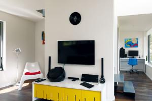"""Barevné akcenty do interiéru vnášejí červené, žluté amodré doplňky, které odkazují na barvy """"včelích úlů"""" vexteriéru. FOTO Dano Veselský"""