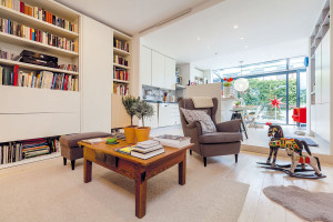 Velkorysá denní část propojuje obývací pokoj skuchyní ajídelní částí, které jsou mírně vyvýšené. Aby se prostor využil co nejfunkčněji, nábytek si nechali majitelé vyrobit na míru. Do převážně bílého interiéru vnášejí barevnost doplňky aživot rodiny. FOTO DANO VESELSKÝ