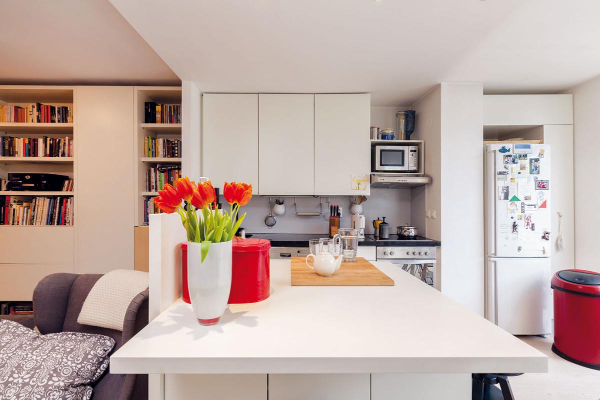 Kuchyň s pracovním ostrovem je laděná podobně jako celá denní část do bílé barvy, což prostor prosvětluje i opticky zvětšuje. K tomu přispívají i uzavřené police, díky čemuž působí úhledně a čistě.
