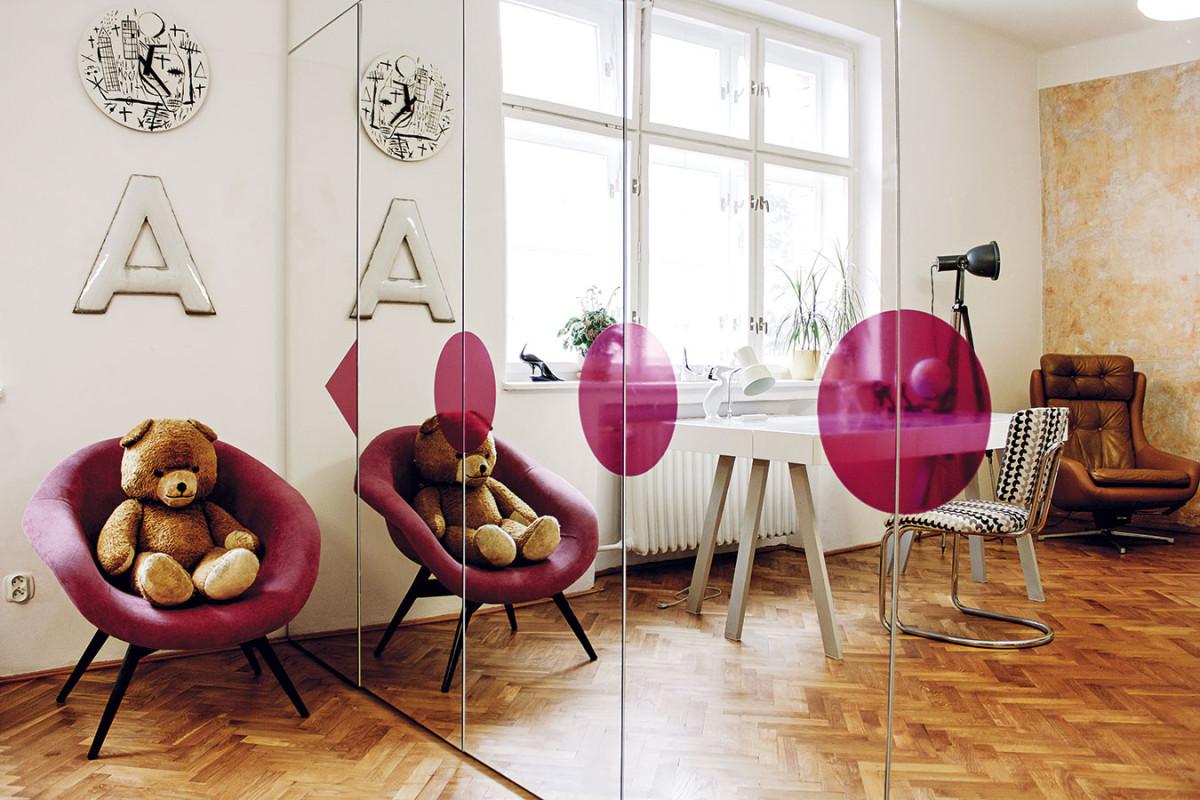 Zrcadlová skříň svelkým grafickým symbolem ladí skřesílkem, které stejně jako pracovní židle prošlo radikální proměnou. Oba kousky se tak chlubí novým čalouněním. FOTO ALEX BELYAJEV