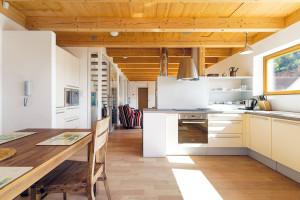Na venkovní terasu navazuje jednoduše aúčelně zařízená kuchyň se stolováním, která je součástí otevřeného denního prostoru na hlavním podlaží. Pás oken umožňuje výhled na jezero zkuchyně izobývacího pokoje. FOTO DANO VESELSKÝ