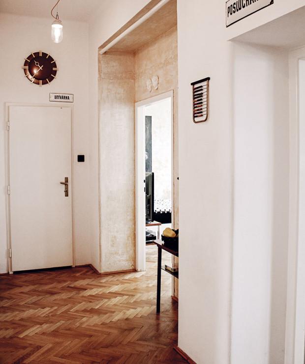 Chodba propojuje všechny místnosti. Univerzální jemné barevné tóny jejích stěn akcentují industriální svítidla, nástěnné hodiny aplechové tabulky. FOTO ALEX BELYAJEV