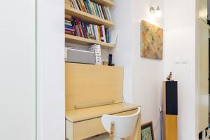 Praktický pracovní koutek se nachází vdenní části bytu aje podobně jako většina nábytku vtomto prostoru vyrobený na míru. Všechny nezbytnosti jsou ukryty přímo ve stolové části. Posuvné dveře nalevo od něj prostor odlehčují. FOTO DANO VESELSKÝ