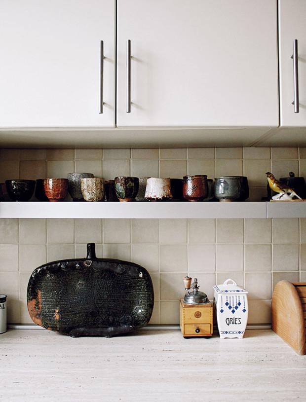 Obklad zkeramických kachliček vizuálně propojuje kuchyňskou linku soriginální škrábanou omítkou, se kterou dokonale barevně ladí. FOTO ALEX BELYAJEV