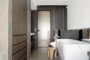 Koupelna jako relaxační místnost vtlumených přírodních barvách. Na pohled idotyk hrubě zpracovaný keramický obklad byl použit velmi omezeně, pouze na podlaze ave sprše, jinak bylo pracováno zejména sdřevěným obkladem amalbou bílým korianem. Doplňkovou barvou je opět zlatá, tentokrát na teakové podnožce. Vana stojí volně vprostoru vedle velkoplošného zrcadla, které vytváří novou prostorovou dimenzi úzké místnosti. Foto Tomáš Vrána