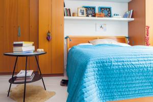 Vrodičovské ložnici je příjemným způsobem zkombinováno dřevo sbílou azářivou modrou barvou. Stolek je domovem knih, kterých je vcelém bytě nespočetně, anahrazuje iten noční. FOTO DANO VESELSKÝ