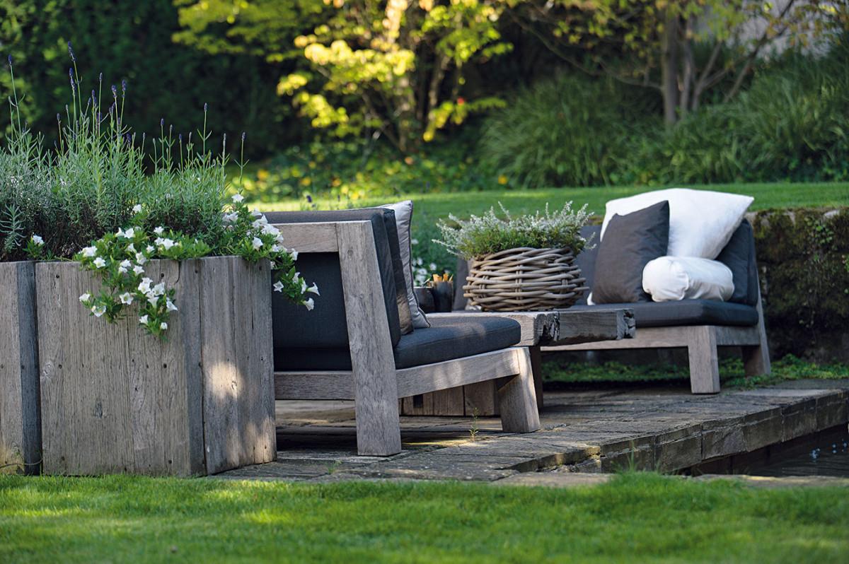 Zahradní nábytek je materiálovým mixem teaku na mohutných stolech alehátkách, šedého proutí na křeslech, koších na byliny ahrubého kamene použitého na velkých květináčích pro byliny. Foto Tomáš Vrána