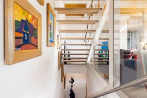 Schodiště zabírá úzký pás useverní zdi domu aod obývacího pokoje ho odděluje skleněná stěna sposuvnými dveřmi – tím se denní prostor oddělil tak, aby se zabránilo únikům tepla, ale zároveň se dlouhá místnost opticky nezúžila. FOTO DANO VESELSKÝ
