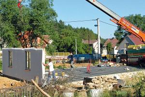 Umisťování panelů na předem připravenou základovou desku – panely se umisťují na vzdálenější stranu od jeřábu, aby měl jeřábník vždy přehled ocelé stavbě.