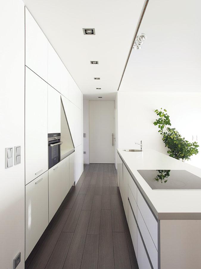 Čistý interiér. Vinteriéru dominuje racionalita, podpořená například dostatkem chytře poskládaných úložných prostor, abílá barevnost, zjemněná prvky viditelné dřevěné konstrukce adřevěné podlahy.